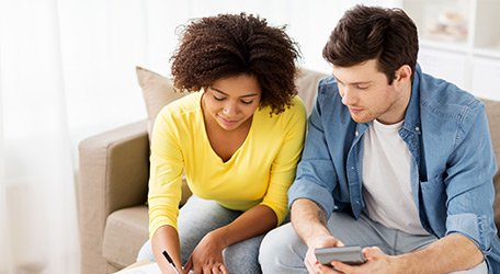 Couple calculating plans on couch