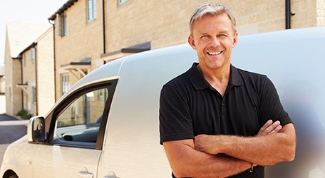 Worker smiling with arms folded outside van