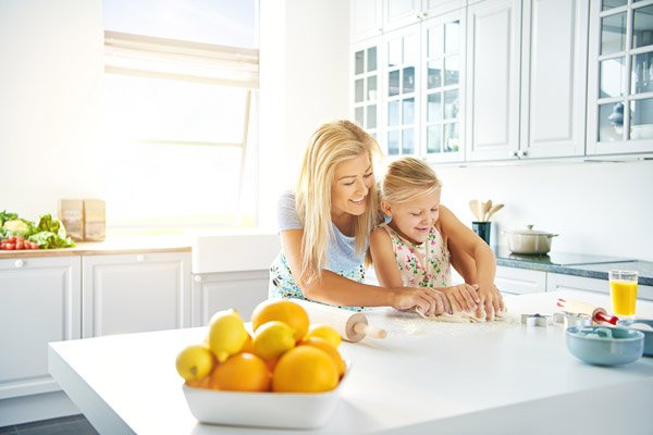 Mother baking with daughter using renewable heating system